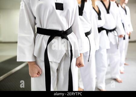 Gros plan des uniformes blancs d'art martial portant des ceintures noires, discipline, dévotion, professionnalisme