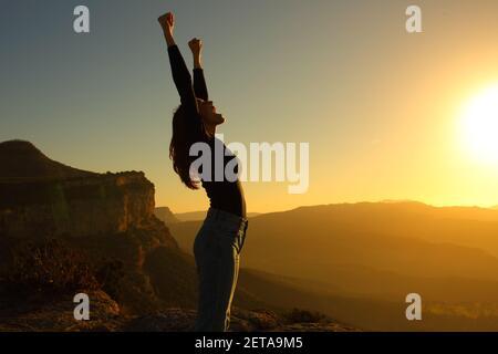 Profil d'une silhouette d'une femme hurlant les bras célébration de vacances au coucher du soleil dans la montagne