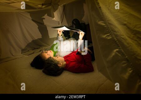 Une femme et un enfant lisant un livre allongé sur une couverture et brillant une lampe de poche de smartphone, dans une tente improvisée dans leur salon. Maison style de vie co