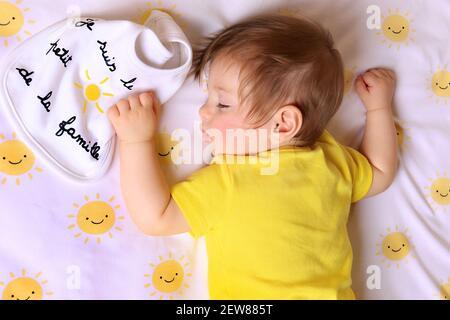 Un bébé tenant un bavoir disant qu'il est le petit soleil de la famille en français.