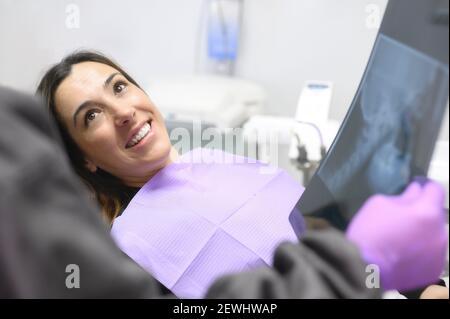 Bonne jeune femme, lors de la consultation avec le dentiste montrant des rayons X dans le cabinet dentaire. Photo de haute qualité.