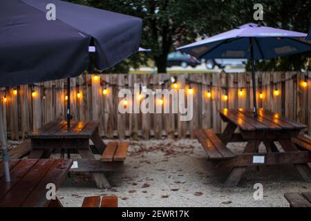 Tables de pique-nique parasols et lumières avec une clôture en bois à l'extérieur Pendant l'hiver en Géorgie Banque D'Images