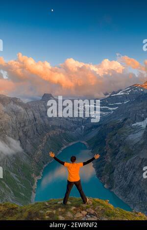Homme aux bras étirés en admirant le coucher du soleil sur le lac Limmernsee, debout au-dessus des rochers, canton de Glaris, Suisse, Europe
