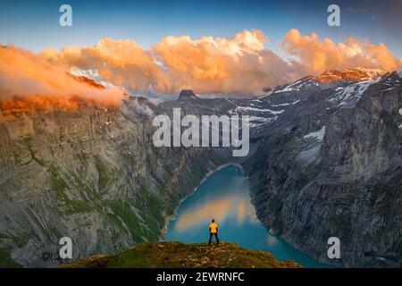 Homme debout sur des rochers regardant les nuages au coucher du soleil sur le lac Limmernsee, vue aérienne, canton de Glaris, Suisse, Europe