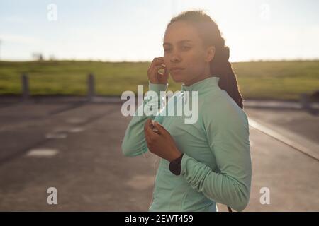 Femme afro-américaine se concentrant, portant des vêtements de sport s'exerçant dans le parc mettant des écouteurs dans