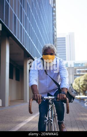 Homme senior afro-américain portant un masque de visage à vélo rue