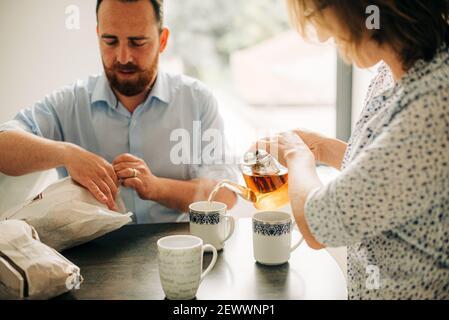 Couple prenant le petit déjeuner avec le thé. Homme ouvrant des sacs avec de la pâte fraîche