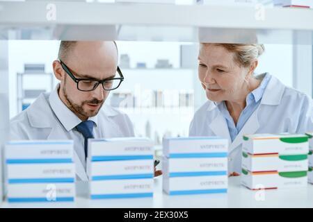 le pharmacien principal et son assistant vérifient les fournitures médicales importantes.