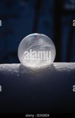 Gros plan de la bulle de savon surgelée sur la neige avec un arrière-plan sombre.