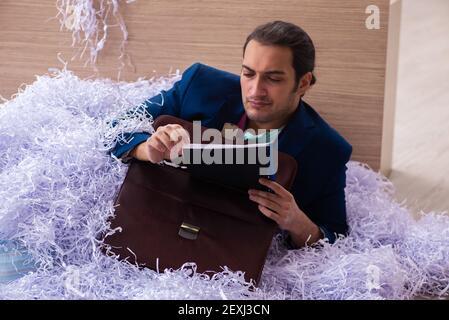 Jeune homme d'affaires et beaucoup de papiers coupés dedans le bureau Banque D'Images
