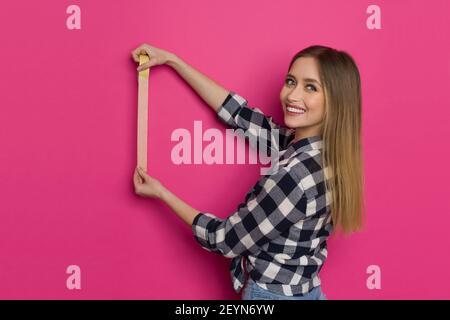 Une jeune femme blonde souriante en chemise de bûcheron tient la bande de peintre jaune sur le mur rose et regarde la caméra. Taille haute.