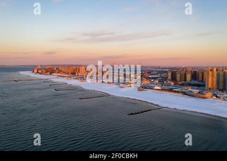 Vue aérienne d'une plage enneigée de Coney Island Beach pendant l'hiver au lever du soleil à Brooklyn, New York.