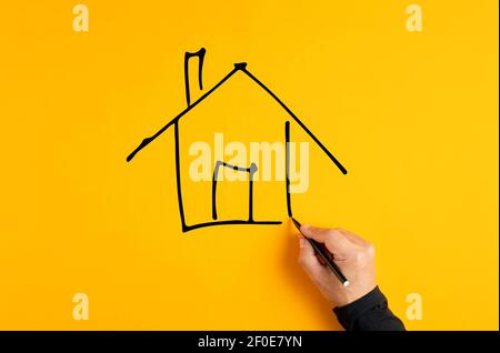 Main masculine dessinant une esquisse de maison sur fond jaune. Concept d'assurance, d'hypothèque ou d'investissement immobilier.