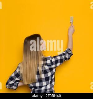 La jeune femme blonde en chemise de bûcherons peint un mur jaune. Vue arrière. Taille haute.