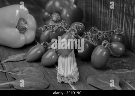 Noir et blanc vue rapprochée des spaghetti de pâtes crues sur fond de bois.légumes frais biologiques avec pâtes non cuites, concept alimentaire sain.