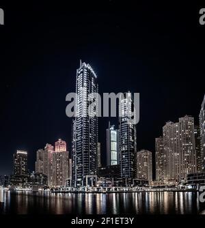 Dubai Marina la nuit avec gratte-ciel, bateaux et réflexions dans l'eau, Émirats arabes Unis Banque D'Images
