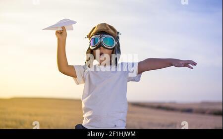 Little Boy wearing helmet et rêve de devenir un aviateur pendant la lecture d'un avion en papier au coucher du soleil