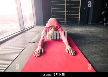 Femme pratiquant le yoga avancé sur un tapis contre une grande fenêtre