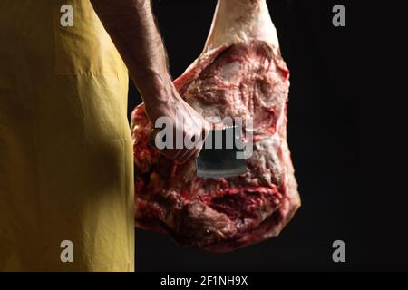 Boucher avec hache de cuisine dans une main et jambe de porc dans l'autre, sur fond noir. Banque D'Images
