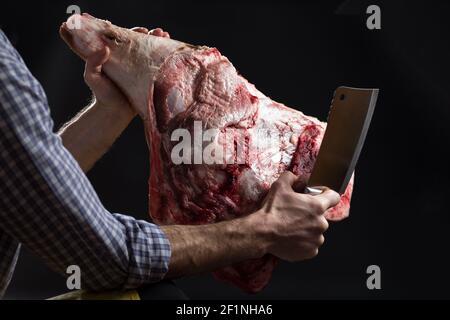 Jambe de porc dans les mains de boucher avec hache de cuisine sur fond noir. Banque D'Images