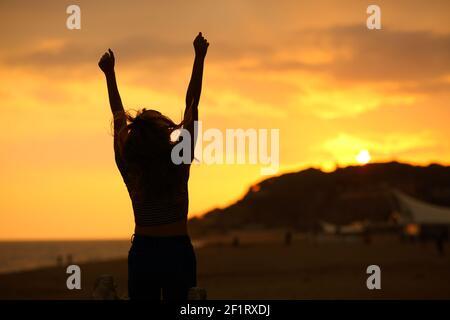 Vue arrière portrait d'une silhouette de femme levant les bras sautant célébration au coucher du soleil sur la plage