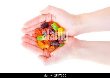 Gros plan des mains femelles pleines d'ours en gelée multicolores isolés sur du blanc.