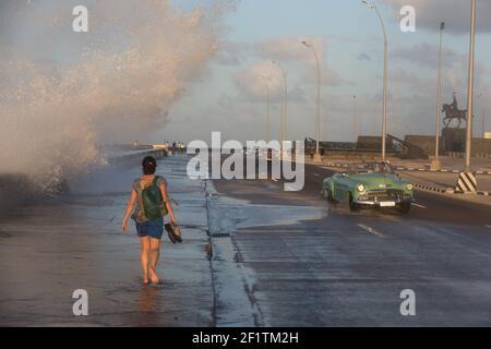 Cuba, la Havane - une voiture s'échappe de peu de l'eau qui s'y éclabousse sur le Malecon. Banque D'Images