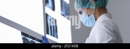 Le médecin en cabinet dans le masque médical de protection et les lunettes regarde l'image de rayons X.