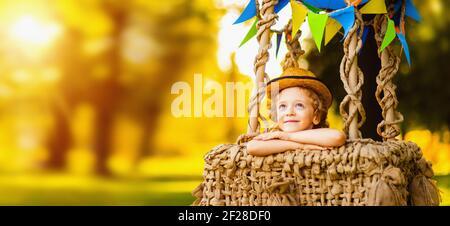 Petit garçon beau assis dans un panier d'un ballon et les rêves regarde dans le ciel.