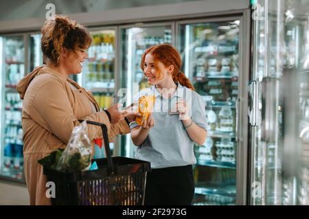 Assistant de magasin aidant la cliente féminine au supermarché. Jeune travailleur aidant une femme à magasiner à l'épicerie.