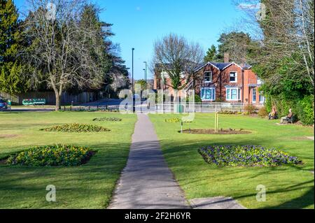 Un sentier menant à Boltro Road à travers Muster Green, un petit parc à Haywards Heath, West Sussex, avec des gens sur des bancs bénéficiant du soleil de printemps.