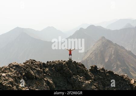 Femme debout avec les bras étendus sur le sommet de la montagne contre ciel dégagé