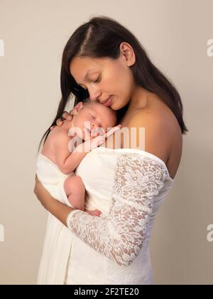 Belle jeune mère dans une robe de dentelle blanche posant avec son fils nouveau-né de 7 jours