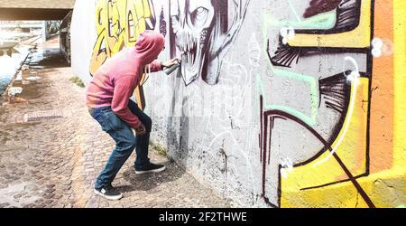 Artiste de rue peignant des graffitis colorés sur le mur public - moderne concept d'art avec un homme urbain qui exécute et prépare des murales en direct