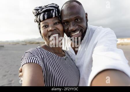 Couple africain heureux prenant selfie sur la plage avec mobile Appareil photo smartphone pendant les vacances d'été - concept de relation d'amour