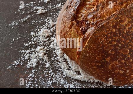 Gros plan de pain maison avec une croûte croustillante sur le table de cuisine arrosée de farine