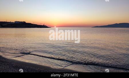 Soleil de lever de soleil orange brillant sur ciel horizon clair sur la côte de la plage de galets près d'Athènes en Grèce. Voyage d'été calme bord de mer le matin