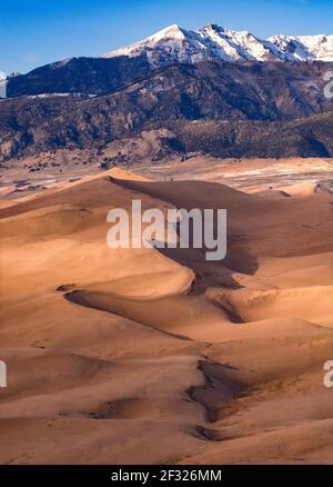 Dune cachée devant les montagnes enneigées de Sangre de Cristo, dans le parc national et réserve de Great Sand Dunes à Hooper, Colorado.