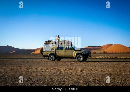 Un photographe au sommet d'un 4x4 dans le désert de sossusvlei, namibie.