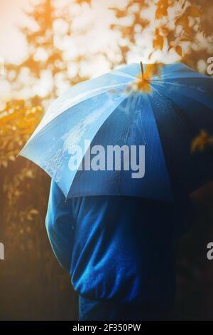 Un homme dans une veste bleue et avec un parapluie bleu dans sa main marche seul dans le parc lors d'un automne ensoleillé pluie jour. Octobre.