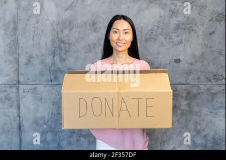 Gentille femme asiatique souriante avec des cheveux droits foncés tenant une boîte en carton, regardant directement la caméra, donnant des vêtements ou des jouets à la charité, pour les orphelins et les sans-abri, pour réutilisation ou recyclage,