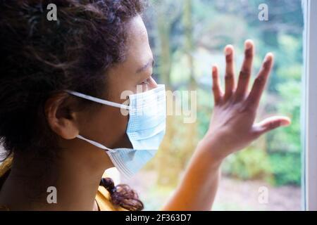 Femme noire inquiète en regardant par la fenêtre
