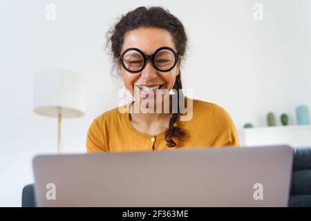 Bonne femme noire qui passe un appel vidéo depuis sa maison Banque D'Images