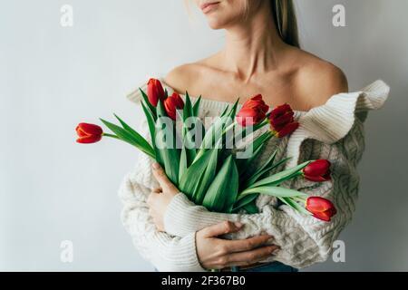 Une jeune femme tient un magnifique bouquet de tulipes rouges dans ses mains.