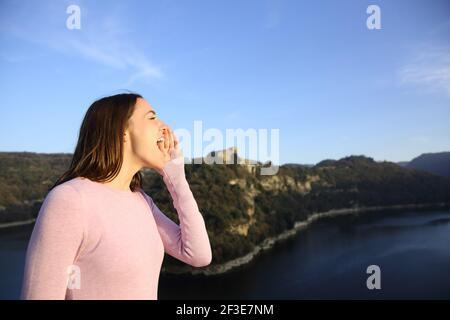 Profil d'une femme heureuse hurlant dans la montagne sur vacances