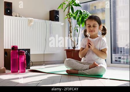 Belle petite fille assise sur un tapis de fitness et pratiquant le yoga en position lotus sur le fond de grandes fenêtres à la maison. Bon P sain
