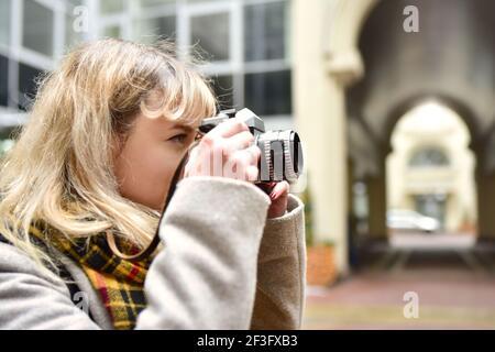 Blonde jolie photographe femme avec un appareil photo rétro dans ses mains tout en prenant des photos à l'architecture urbaine ancienne. Découvrez de nouveaux lieux.