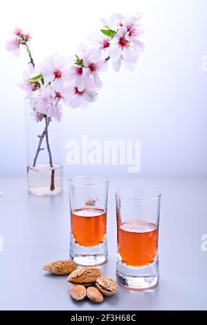 liqueur d'amande. La boisson traditionnelle forte en italie pour compléter le dîner est une liqueur à base de noix et de baies. Ratafia, alcool en grenaille. Sur la table et une branche d'amandes en fleurs. Copier l'espace