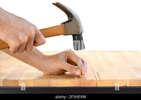 Marteler un clou à la main sur une table en bois