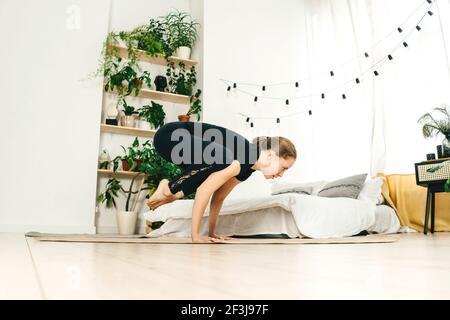 Portrait d'une belle jeune femme pratiquant le yoga à l'intérieur. Femme en vêtements de sport noirs s'entraîner à la maison légère. Lit et plantes vertes à la maison sur fond.
